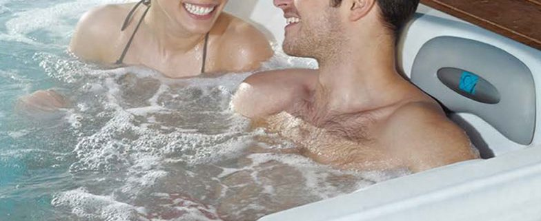 Couple relaxing in their hot tub by Artesian Spas