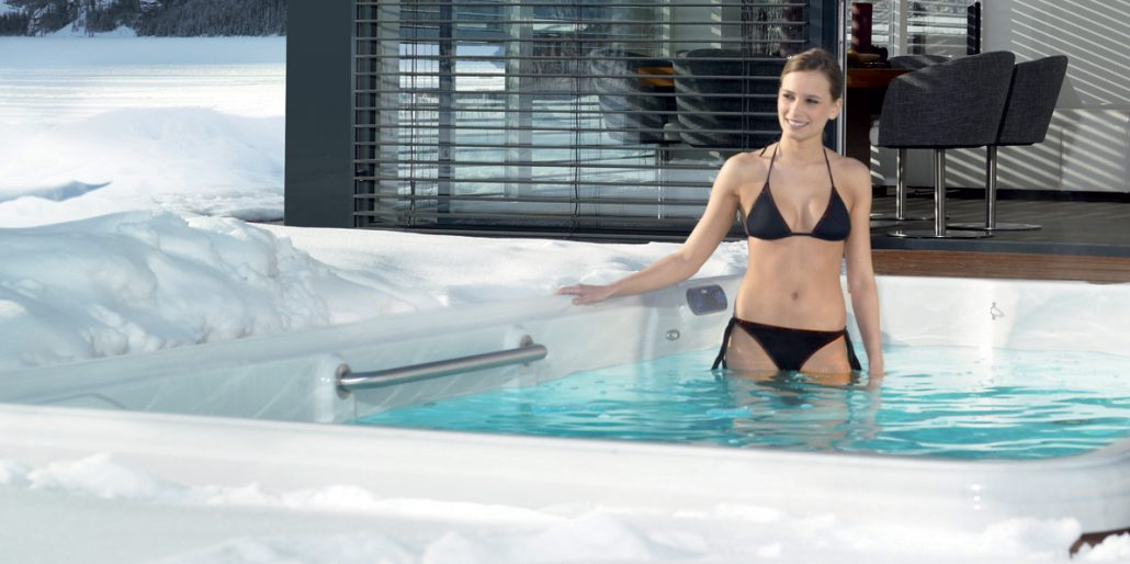 Woman entering her TidalFit exercise pool on winter day