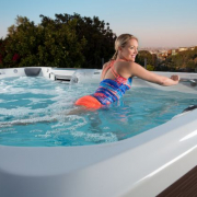 Lady Exercising in Swim Spa that an athlete would use for recovery and performance.